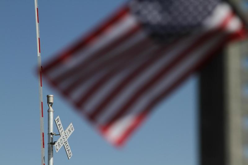 A flag flies at the scene of an accident where four veterans were killed and 16 other people were injured when a train slammed into a parade float carrying the returning heroes to a banquet last Thursday in Midland, Texas on Saturday, Nov. 17, 2012. Federal investigators were trying to determine whether the two-float parade had been given enough warning to clear the tracks. (AP Photo/Juan Carlos Llorca)
