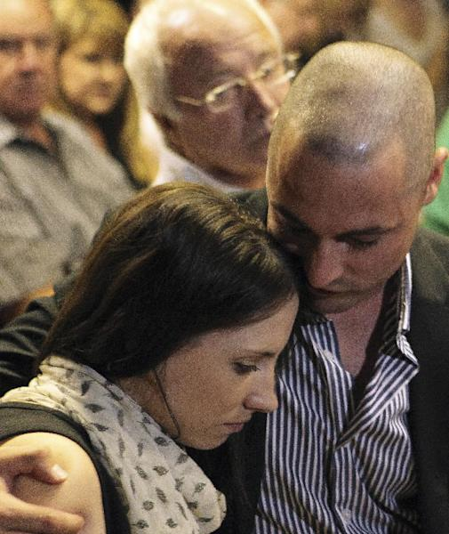 Olympic athlete Oscar Pistorius's brother Carl Pistorius, right, comforts sister Aimee, left, during the bail application at the magistrate court in Pretoria, South Africa, Tuesday, Feb. 19, 2013, and with his father Henke Pistorius seen at top centre. Oscar Pistorius faces a bail hearing charged with the shooting death of his girlfriend Reeva Steenkamp. (AP Photo/Themba Hadebe)