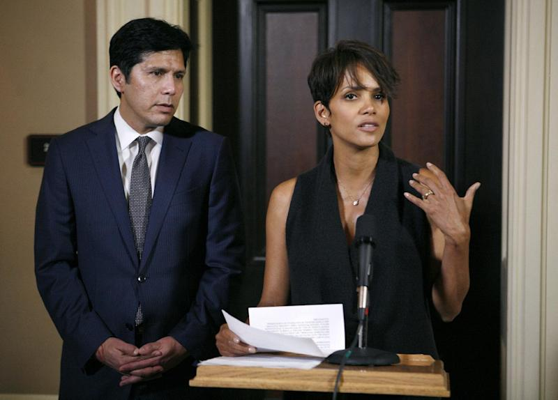 Actress Halle Berry, right, talks to reporters at a news conference before testifying at an Assembly Committee on Public Safety hearing for a bill that would limit the ability of paparazzi to photograph the children of celebrities and public figures at the Capitol in Sacramento, Calif., on Tuesday, June 25, 2013. At the left is Sen. Kevin DeLeon, D-Los Angles, the author of the bill.(AP Photo/Steve Yeater)