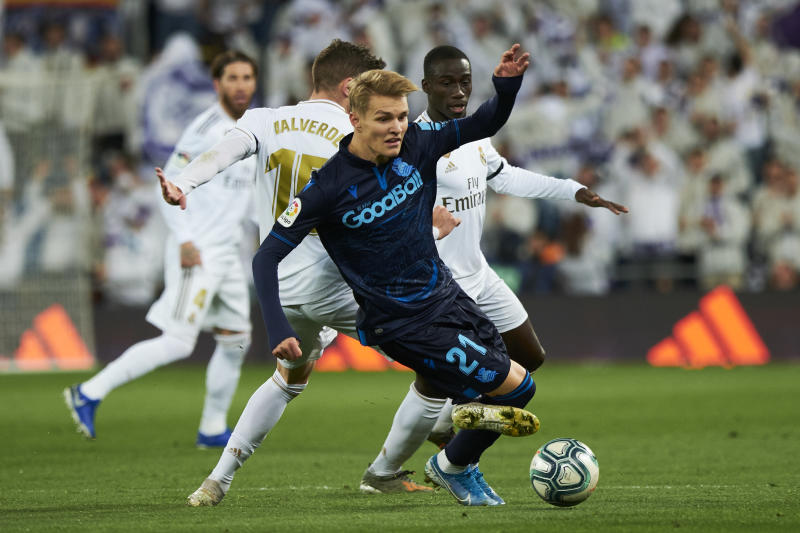 MADRID, SPAIN - NOVEMBER 23: Midfielder Martin Odegaard of Real Sociedad gets tackled by Midfielder Federico Valverde of Real Madrid CF during the Liga match between Real Madrid CF and Real Sociedad at Estadio Santiago Bernabeu on November 23, 2019 in Madrid, Spain. (Photo by Xaume Olleros/Getty Images)