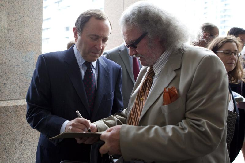 National Hockey League commissioner Gary Bettman, left, signs an autograph as he arrives for collective bargaining talks in Toronto on Wednesday, Aug. 15, 2012. (AP Photo/The Canadian Press, Chris Young)