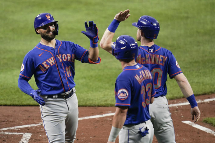 New York Mets' Kevin Pillar (11) is greeted near home pate by James McCann (33) and Billy McKinney after Pillar scored them all on a three-run home run off Baltimore Orioles starting pitcher Matt Harvey during the third inning of a baseball game, Wednesday, June 9, 2021, in Baltimore. (AP Photo/Julio Cortez)