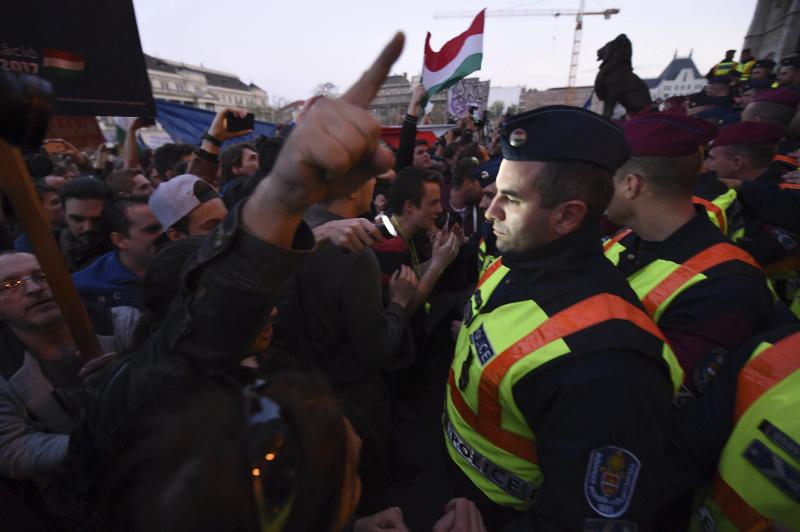 """Demonstrators argue with police officers protecting near the Parliament building protesting against the amendment of the higher education law that could force a Budapest university founded by billionaire American philanthropist George Soros to close , in front of the Parliament building in Budapest, Hungary, Sunday, April 9, 2017. Hungarian President Janos Ader said Monday April 9, 2017, in a statement that he has signed the bill setting new conditions for foreign universities in Hungary which is in line with the Constitution, and called on the government to """"immediately"""" begin talks with the affected institutions to secure compliance with the new rules. (Zoltan Balogh/MTI via AP)"""