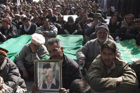 A Shi'ite Muslim man holds a picture of his relative as he sits beside the covered bodies of other victims who were killed in Tuesday's night bomb attack on a bus, during a protest in the provincial capital of Quetta January 22, 2014. REUTERS/Naseer Ahmed