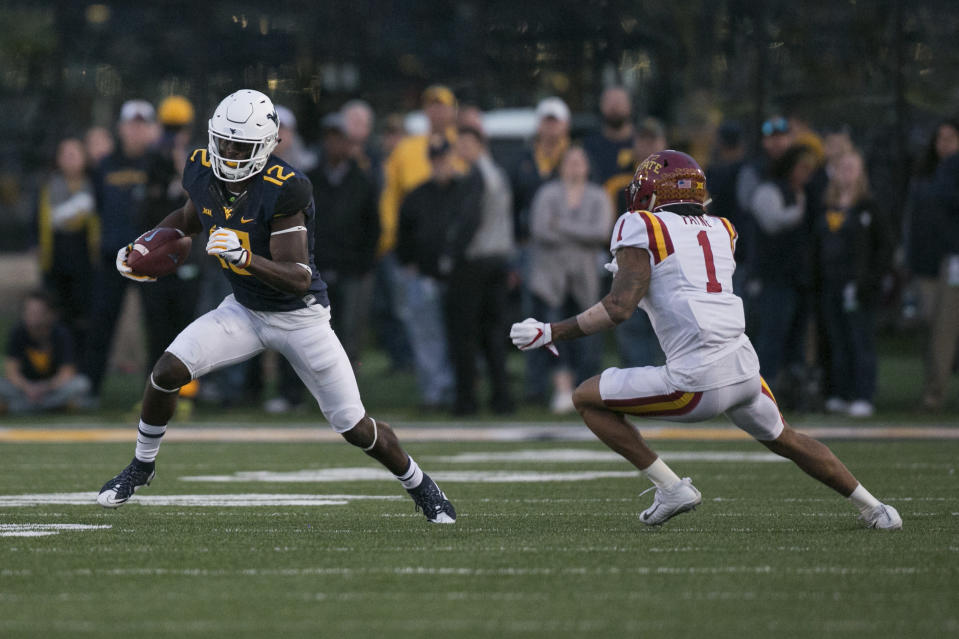 West Virginia wide receiver Gary Jennings (12) avoids Iowa State's D'Andre Payne (1) during the second half of an NCAA college football game against Iowa State in Morgantown, W.Va., Saturday, Nov. 4, 2017. (AP Photo/Walter Scriptunas II)