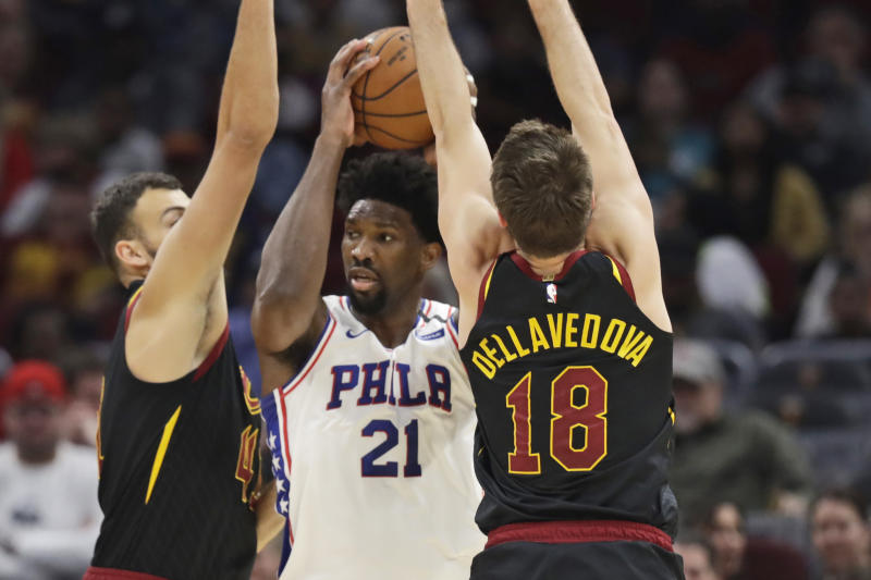 Philadelphia 76ers' Joel Embiid, center, squeezes between Cleveland Cavaliers' Ante Zizic, left and Matthew Dellavedova in the first half of an NBA basketball game, Wednesday, Feb. 26, 2020, in Cleveland. (AP Photo/Tony Dejak)