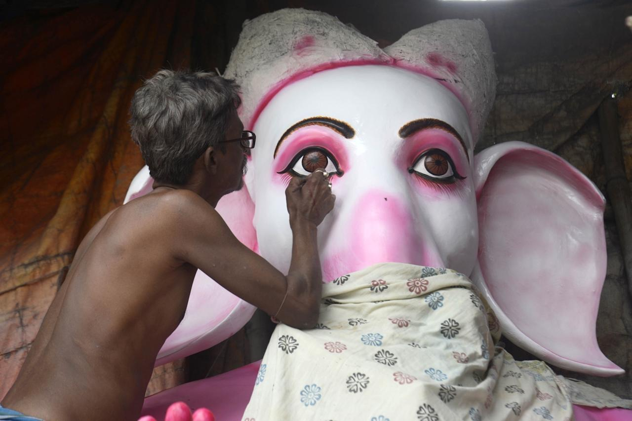 <p>An artist busy giving finishing touches to an idol of Lord Ganesha on the eve of Ganesh Chaturthi, in Kolkata, on September 12, 2018. (Photo: IANS) </p>