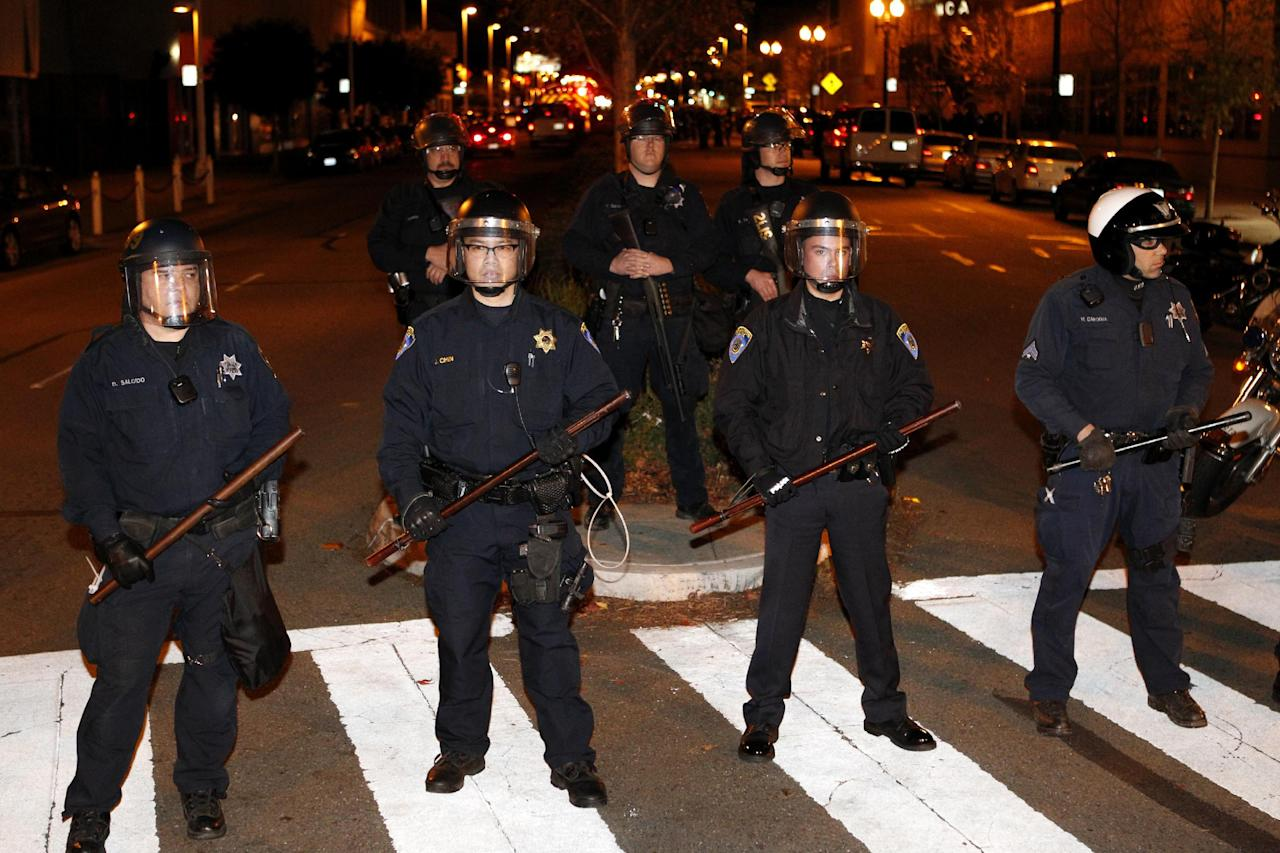 Oakland police block off a street in downtown Oakland during an Occupy Oakland protest, Saturday, January 28, 2012, in Oakland, Calif. Police were in the process of arresting about 100 Occupy protesters for failing to disperse Saturday night, hours after officers used tear gas on a rowdy group of demonstrators who threw rocks and flares at them and tore down fences. (AP Photo/Beck Diefenbach)
