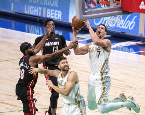 Miami Heat forward Maurice Harkless (8) grabs the arm of Dallas Mavericks center Dwight Powell (7), who goes up for a shot, while Mavericks' Maxi Kleber and Heat's Bam Adebayo (13) watch during the first half of an NBA basketball game Friday, Jan. 1, 2021, in Dallas. (AP Photo/Jeffrey McWhorter)
