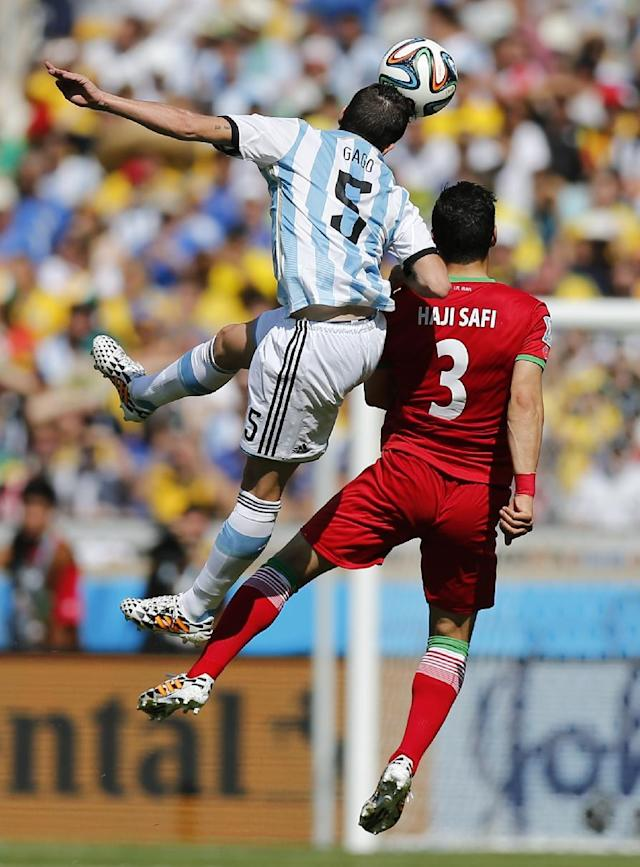 Argentina's Fernando Gago, left, challenges Iran's Ehsan Haji Safi during the group F World Cup soccer match between Argentina and Iran at the Mineirao Stadium in Belo Horizonte, Brazil, Saturday, June 21, 2014. (AP Photo/Victor R. Caivano)
