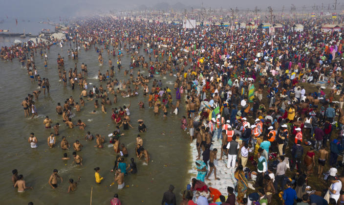 """Hindu devotees gather at the Sangam, the confluence of the rivers Ganges and the Yamuna, during the annual month long Hindu religious fair """"Magh Mela"""" In Prayagraj, India, Thursday, Feb. 11, 2021. When the coronavirus pandemic took hold in India, there were fears it would sink the fragile health system of the world's second-most populous country. Infections climbed dramatically for months and at one point India looked like it might overtake the United States as the country with the highest case toll. But infections began to plummet in September, and experts aren't sure why. (AP Photo/Rajesh Kumar Singh)"""
