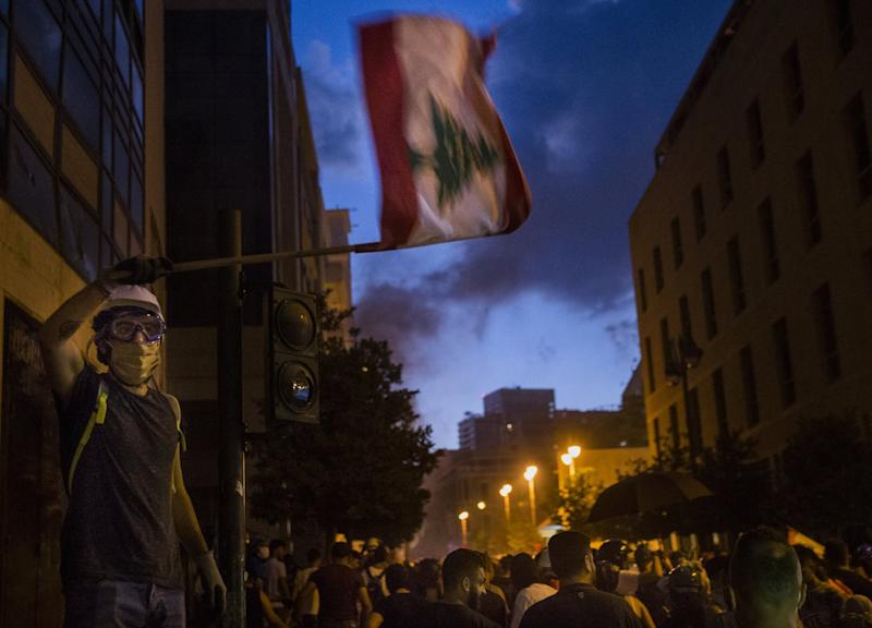 A protestor waves the Lebanese flag while protesting near Martyrs Square: Getty Images