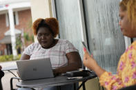 Francesca Menes, left, and Krystina Francois, children of Haitian immigrants to the U.S. and co-founders of the Black Collective, work together outside a Starbucks, Tuesday, Sept. 21, 2021, in Miami Shores, Fla. Menes and Francois, whose advocacy organization focuses on the political needs and economic empowerment of Black people across the African diaspora, have called for the Biden administration to immediately suspend plans to remove migrants via planes bound for Haiti. (AP Photo/Rebecca Blackwell)