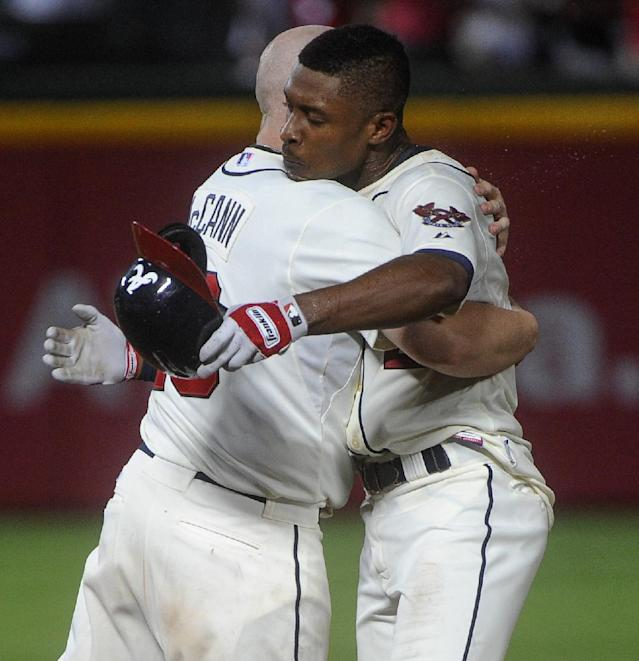 Atlanta Braves' B.J. Upton right celebrates his game-winning run with Brian McCann in the 11th inning against the Miami Marlins during a baseball game, Saturday, Aug. 31, 2013, in Atlanta. Atlanta won 5-4. (AP Photo/John Amis)
