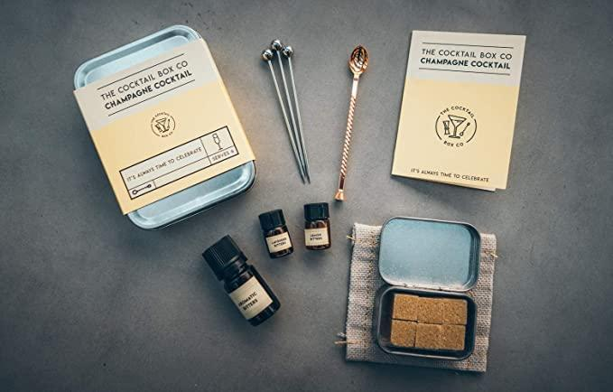 """<h3><h2>The Cocktail Box Co. Champagne Cocktail Kit </h2></h3><br>Make mid-air happy hour more festive with help from this TSA-approved, champagne cocktail tin — each six-drink kit comes with a linen cocktail napkin, muddler spoon, stainless steel cocktail pins, raw cane sugar cubes, lavender bitters, lemon bitters, and aromatic bitters.<br><br><em>Shop</em> <strong><em><a href=""""https://amzn.to/3ogb1Ot"""" rel=""""nofollow noopener"""" target=""""_blank"""" data-ylk=""""slk:The Cocktail Co."""" class=""""link rapid-noclick-resp"""">The Cocktail Co.</a></em></strong><br><br><strong>The Cocktail Box Co.</strong> Premium Cocktail Kit, $, available at <a href=""""https://amzn.to/3bJEgnZ"""" rel=""""nofollow noopener"""" target=""""_blank"""" data-ylk=""""slk:Amazon"""" class=""""link rapid-noclick-resp"""">Amazon</a>"""