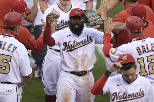 Washington Nationals' Josh Harrison, center, celebrates after the first baseball game of a doubleheader against the New York Mets, Saturday, Sept. 26, 2020, in Washington. The game was a makeup from Sept. 25. (AP Photo/Nick Wass)