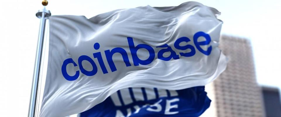 Flags of Coinbase and NYSE flying in the wind. On April 14, 2021, Coinbase went public on the Nasdaq exchange.