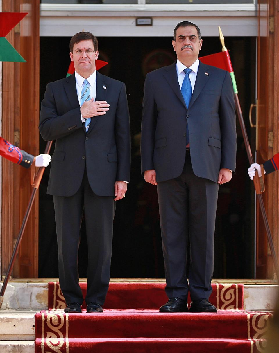 Iraqi Defense Minister Najah al-Shammari, right, and U.S. Defense Secretary Mark Esper, left, stand for their country's national anthems during a welcome ceremony at the Ministry of Defense, Baghdad, Iraq, Wednesday, Oct. 23, 2019. Esper has arrived in Baghdad on a visit aimed at working out details about the future of American troops that are withdrawing from Syria to neighboring Iraq. (AP Photo/Hadi Mizban)
