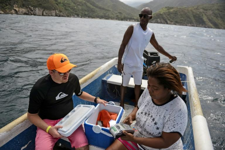 Nancy Rodriguez charges food to a tourist's credit card in a boat, after motoring two km off Chichiriviche de la Costa, to find an internet signal, some 70 km northwest of Caracas on January 13, 2018