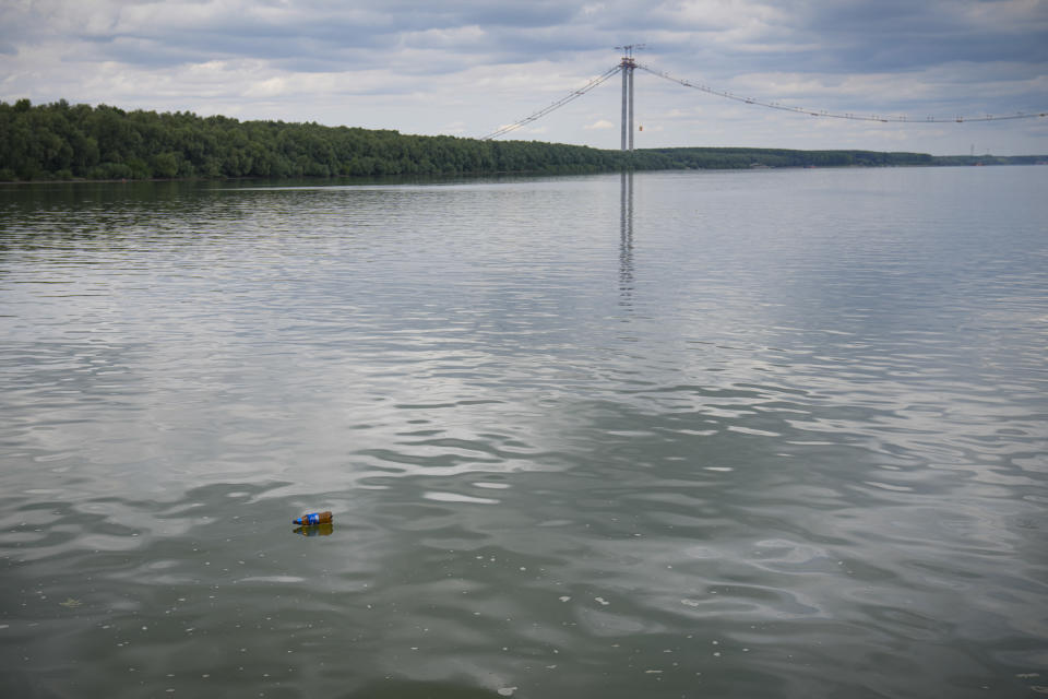 A plastic bottle floats on the water during a ceremony marking 100 years of diplomatic relations between Japan and Romania, at the construction site of a suspension bridge over the Dnube river, seen in the background, in Braila, Romania, Thursday, Aug. 26, 2021. The bridge, built by Japanese and Italian companies, with a span of 1,974.3 meters, will be the largest of its kind in Romania and the third in the European union.(AP Photo/Vadim Ghirda)