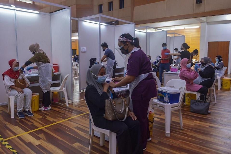 Foreign workers receive their Covid-19 vaccination at Komplek Sukan PKNS in Kelana Jaya August 10, 2021. — Picture by Miera Zulyana