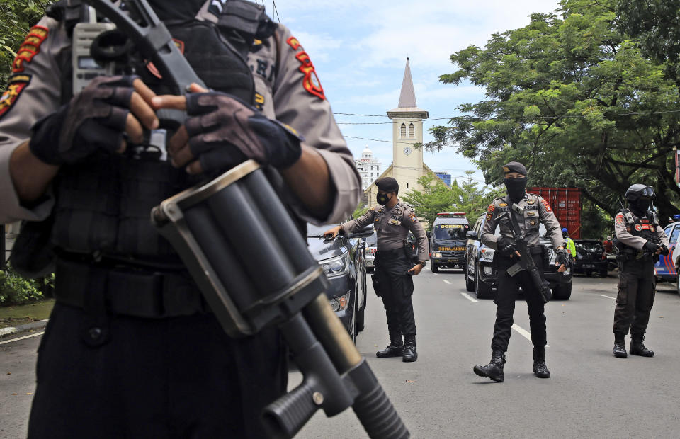 Police officers stand guard near a church where an explosion went off in Makassar, South Sulawesi, Indonesia, Sunday, March 28, 2021. (AP Photo/Yusuf Wahil)