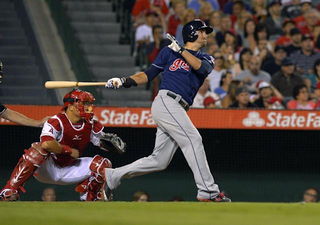 Cleveland Indians' Lonnie Chisenhall, right, hits a two-run home run as Los Angeles Angels catcher Hank Conger looks on during the fourth inning of their baseball game, Monday, Aug. 19, 2013, in Anaheim, Calif. (AP Photo/Mark J. Terrill)