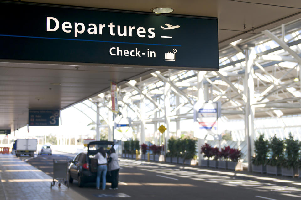 Sydney International Airport departures sign during the day with a car parked nearby and a suitcase being taken out.