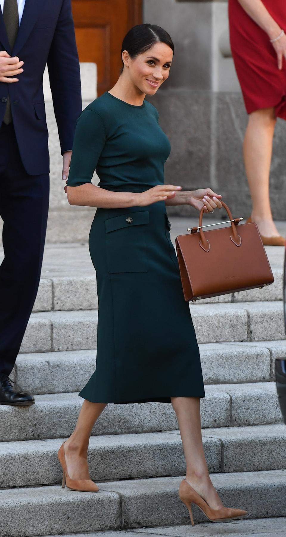 In a look reminiscent of her 'Suits' days, the Duchess of Sussex wore a suitably Irish green Givenchy dress for a trip to the Emerald Isle. A £545 Strathberry midi tote finished the look. <em>[Photo: Getty]</em>