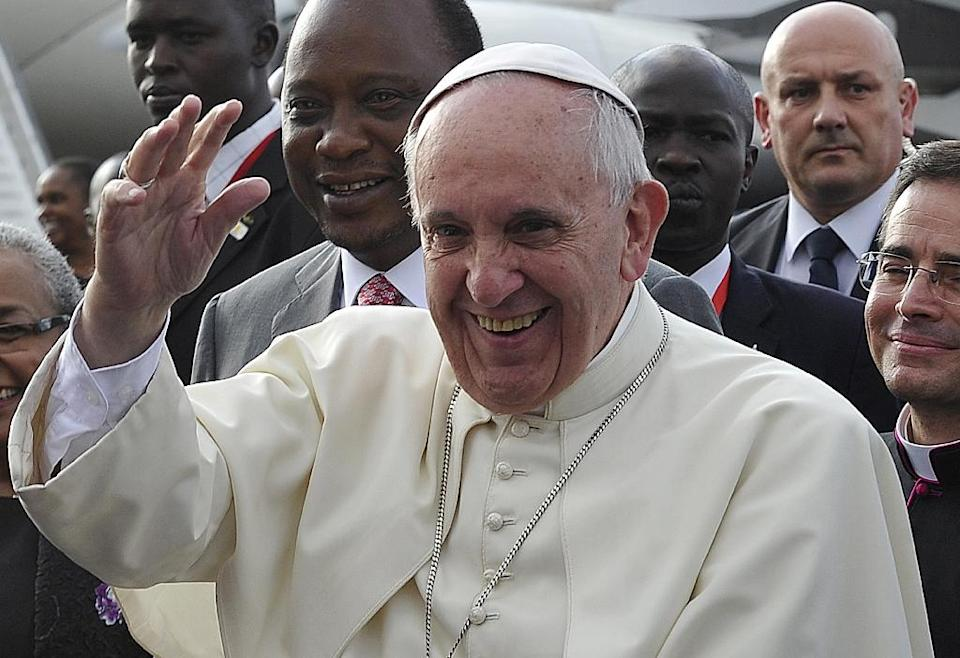 Pope Francis (R), followed by Kenya's President Uhuru Kenyatta, waves as he arrives at the international airport in Nairobi on November 25, 2015 (AFP Photo/Simon Maina)