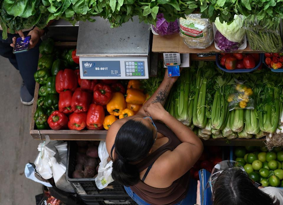 A woman pays for groceries at the municipal market of Chacao in Caracas amid the COVID-19 novel coronavirus pandemic, on September 3, 2020 as inflation increases in Venezuela which is in the midst of the worst economic crisis in its history after seven years of recession. - Venezuela is sitting on the world's largest proven oil reserves but under Nicolas Maduro's watch, the country has descended into crisis. Poverty has soared, inflation is the highest in the world, the currency has become practically worthless, and oil production is down to its lowest level in 77 years, which experts blame on mismanagement and corruption. (Photo by Federico PARRA / AFP) (Photo by FEDERICO PARRA/AFP via Getty Images)