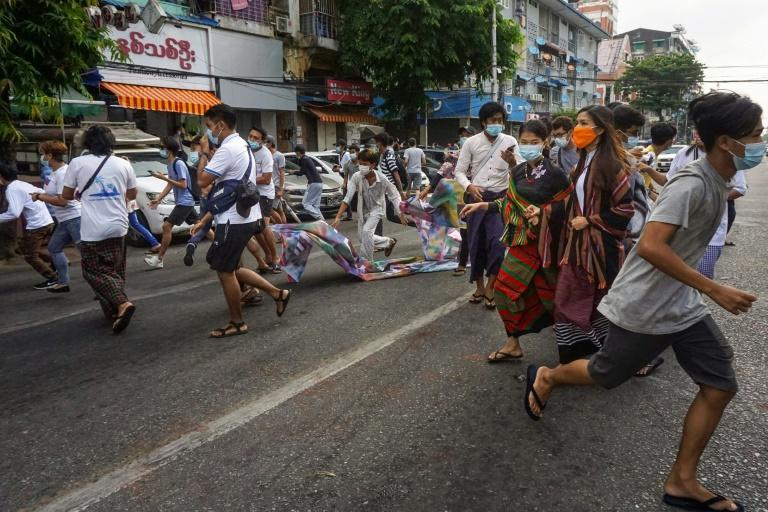 Protesters run from security forces during a demonstration against the military coup in Yangon on June 3, 2021
