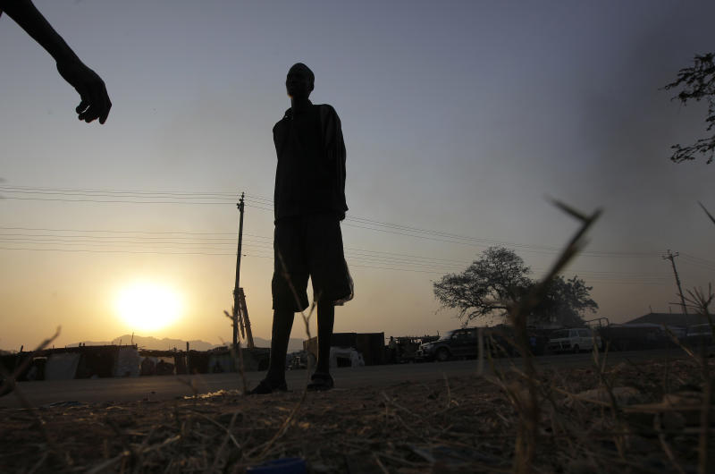 A tall Sudanese man walks past  the John Garang mausoleum where a polling station is being set up in  Juba, Southern Sudan, Saturday Jan. 8, 2011.  Southern Sudan begins voting in a weeklong independence referendum Sunday that is likely to see Africa's largest country split in two. In order for the referendum to pass, a simple majority must vote for independence and 60 percent of the 3.9 million registered voters must cast ballots. (AP Photo/Jerome Delay)