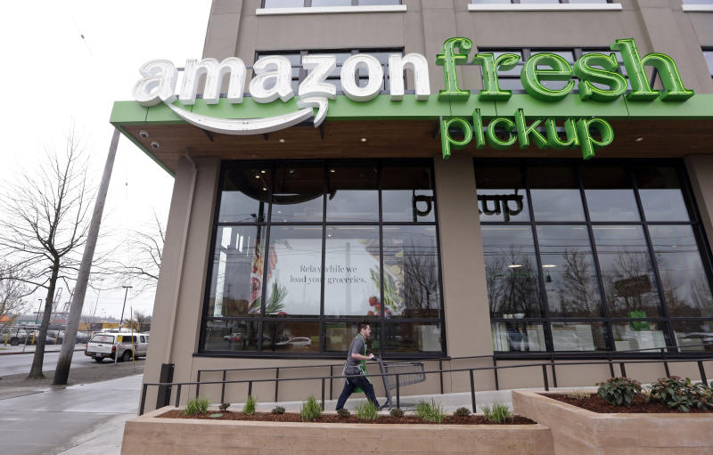 FILE - In this Tuesday, March 28, 2017, file photo, an Amazon worker wheels back a cart after loading a bag of groceries into a customer's car at an AmazonFresh Pickup location in Seattle. Amazon.com Inc. reports financial earnings Thursday, April 27, 2017. (AP Photo/Elaine Thompson, File)