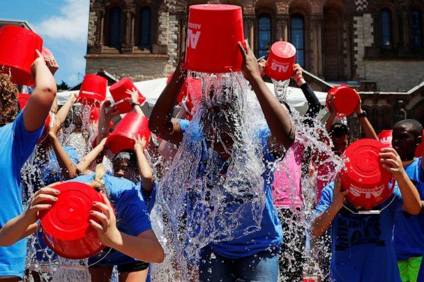PHOTO: In this July 15, 2019, file photo, eleven-year-old Jahziyah Jones, with a crowd of others, pours a bucket of ice water over her head during an event to commemorate the five year anniversary of the 'ALS Ice Bucket Challenge,' in Boston. (Brian Snyder/Reuters, FILE)