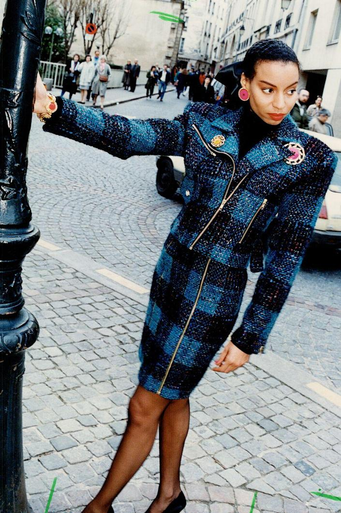 <p>A model dons a blue tweed skirt suit on the street. </p>