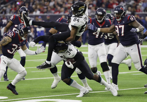 Jacksonville Jaguars running back Carlos Hyde (34) upends teammate Keelan Cole (84) as he runs against the Houston Texans during the second half of an NFL football game, Sunday, Dec. 30, 2018, in Houston. (AP Photo/David J. Phillip)