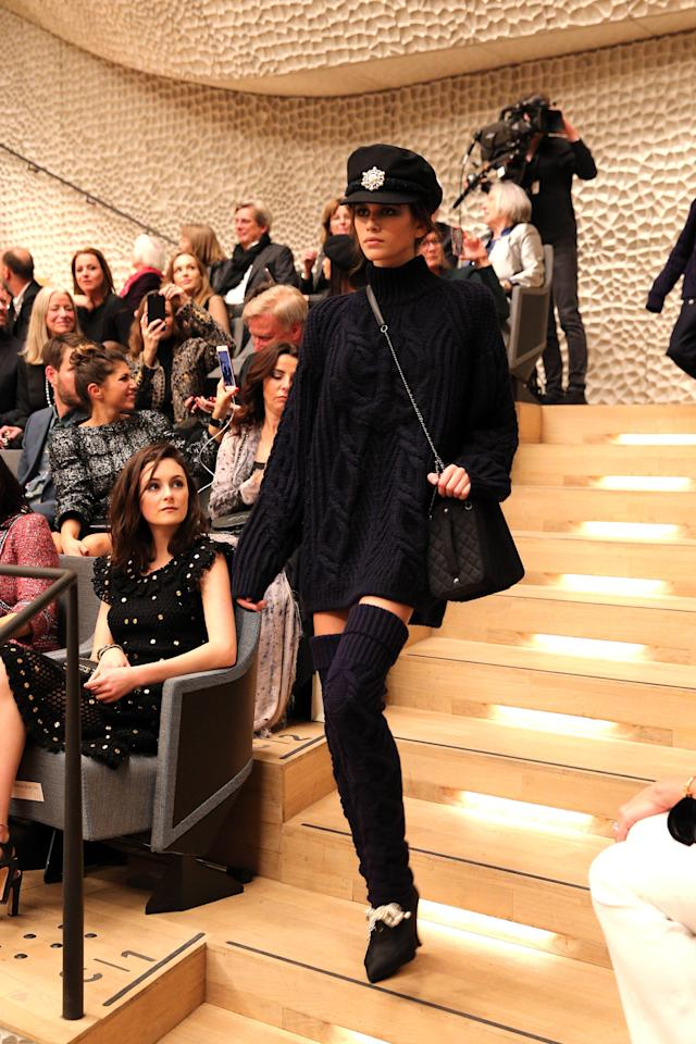 <p>Model Kaia Gerber walks again at the Chanel Métiers d'Art show wearing a black knit sweater, leg warmers, a sailor cap, and a cross-body bag. (Photo: Getty Images) </p>