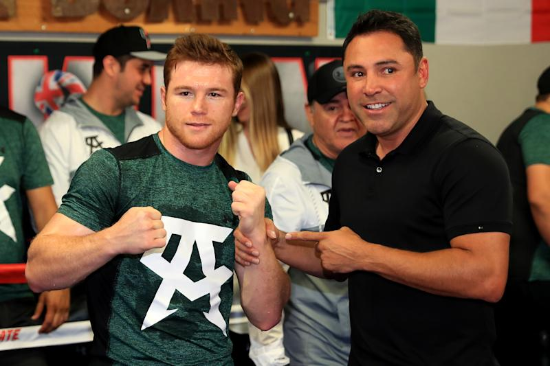 SAN DIEGO, CA - APRIL 25: WBC middleweight champion Canelo Alvarez poses with Chairman and CEO of Golden Boy Productions Oscar De La Hoya during a media workout at the House of Boxing Gym on April 25, 2016 in San Diego, California. (Photo by Sean M. Haffey/Getty Images)