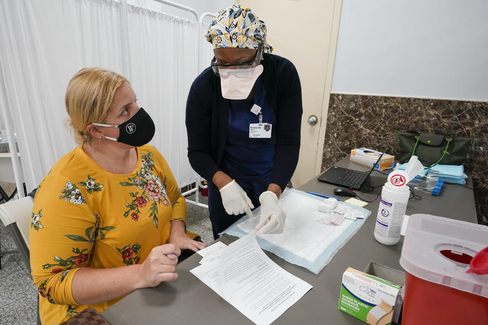 A Northwell Health registered nurse goes over the paper work with mosque member Zejreme Rodoncic after inoculating her with the Johnson & Johnson COVID-19 vaccine at a pop up vaccinations site the Albanian Islamic Cultural Center, Thursday, April 8, 2021, in the Staten Island borough of New York. Ahead of Ramadan, Islamic leaders are using social media, virtual town halls and face-to-face discussions to spread the word that it's acceptable for Muslims to be vaccinated during daily fasting that happens during the holy month. (AP Photo/Mary Altaffer)