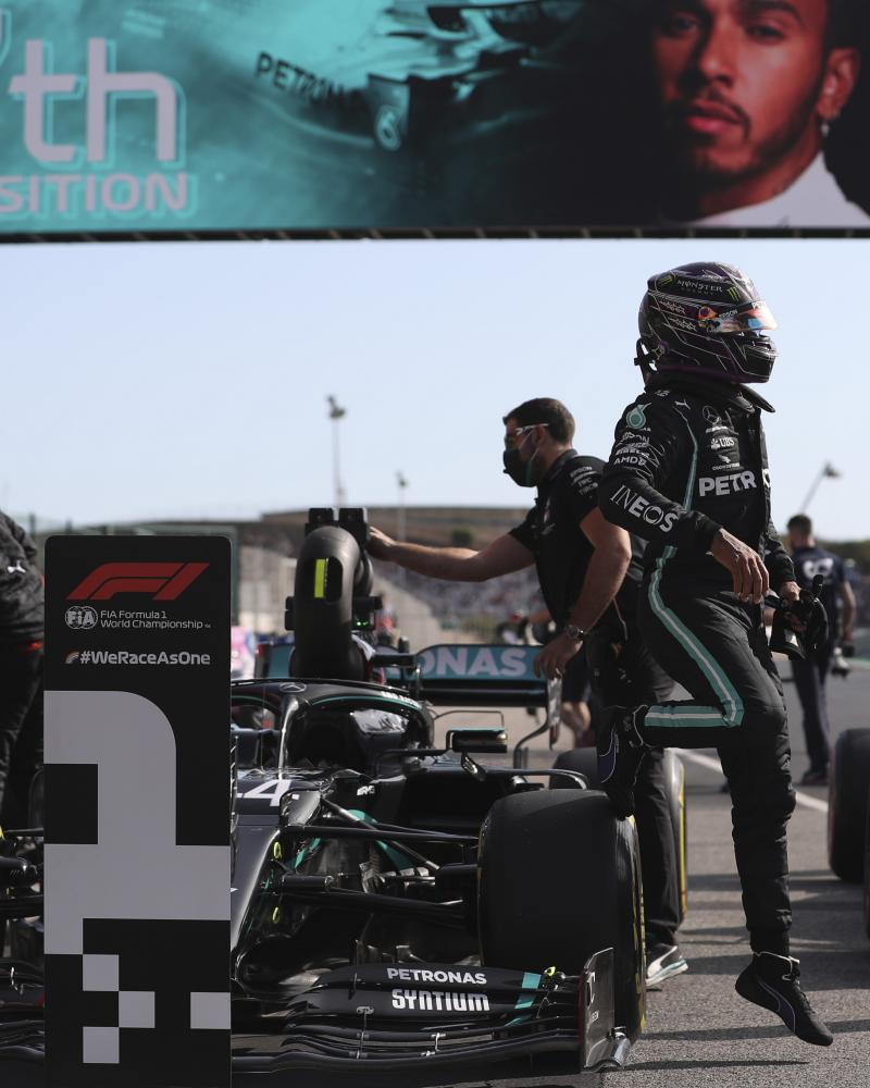 Lewis Hamilton climbs out of his Mercedes after parking it up by the pole-sitter's board