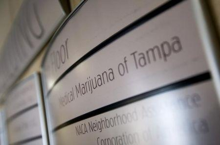 An office building sign directs visitors to Florida's first marijuana business school, Medical Marijuana Tampa, in Tampa, Florida