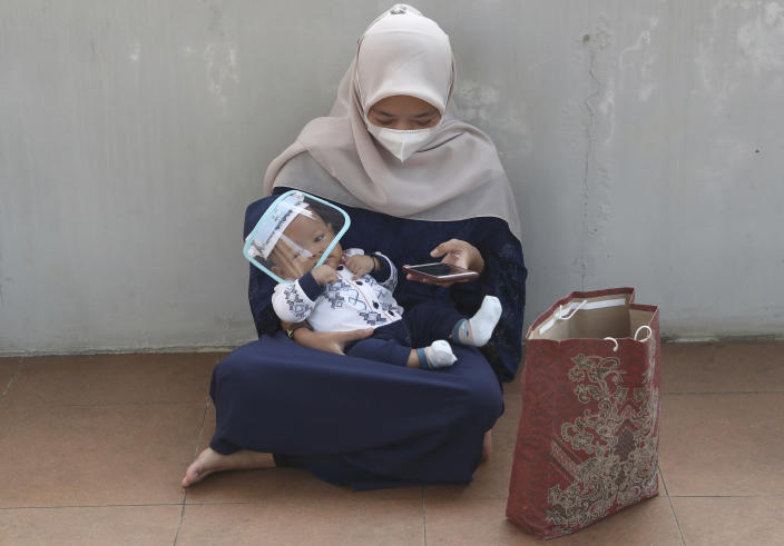 A woman wearing a face mask to curb the spread of coronavirus with her baby attends during an Eid al-Adha prayer at Zona Madina mosque in Bogor, Indonesia,Tuesday, July 20, 2021. Muslims across Indonesia marked a grim Eid al-Adha festival for a second year Tuesday as the country struggles to cope with a devastating new wave of coronavirus cases and the government has banned large gatherings and toughened travel restrictions. (AP Photo/Tatan Syuflana)