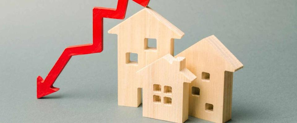 Miniature wooden houses and a red arrow down. The concept of lower mortgage rates.