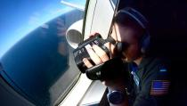 FILE PHOTO: A member of the US Navy, aboard the Boeing P-8A Poseidon plane, looks down as they fly over the South Atlantic Ocean during the search for the ARA San Juan submarine missing at sea