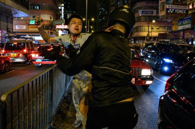 An unidentified man holds a brick as he fights with a group of people after a flashmob rally in Hong Kong, a day after the city's leader outlawed face coverings at protests (AFP Photo/Philip FONG)