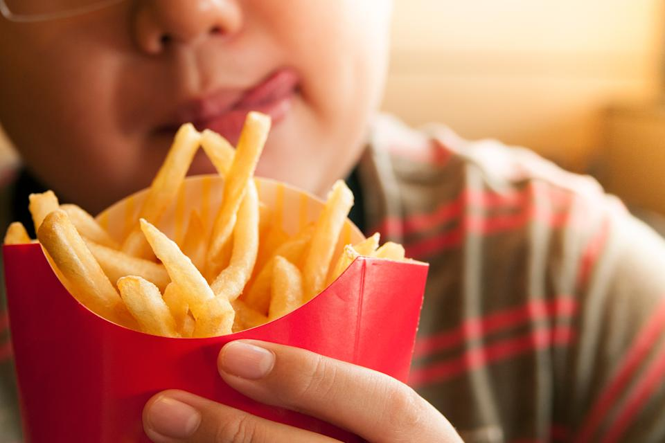 Cropped Image Of Tempted Boy Holding French Fries Packet