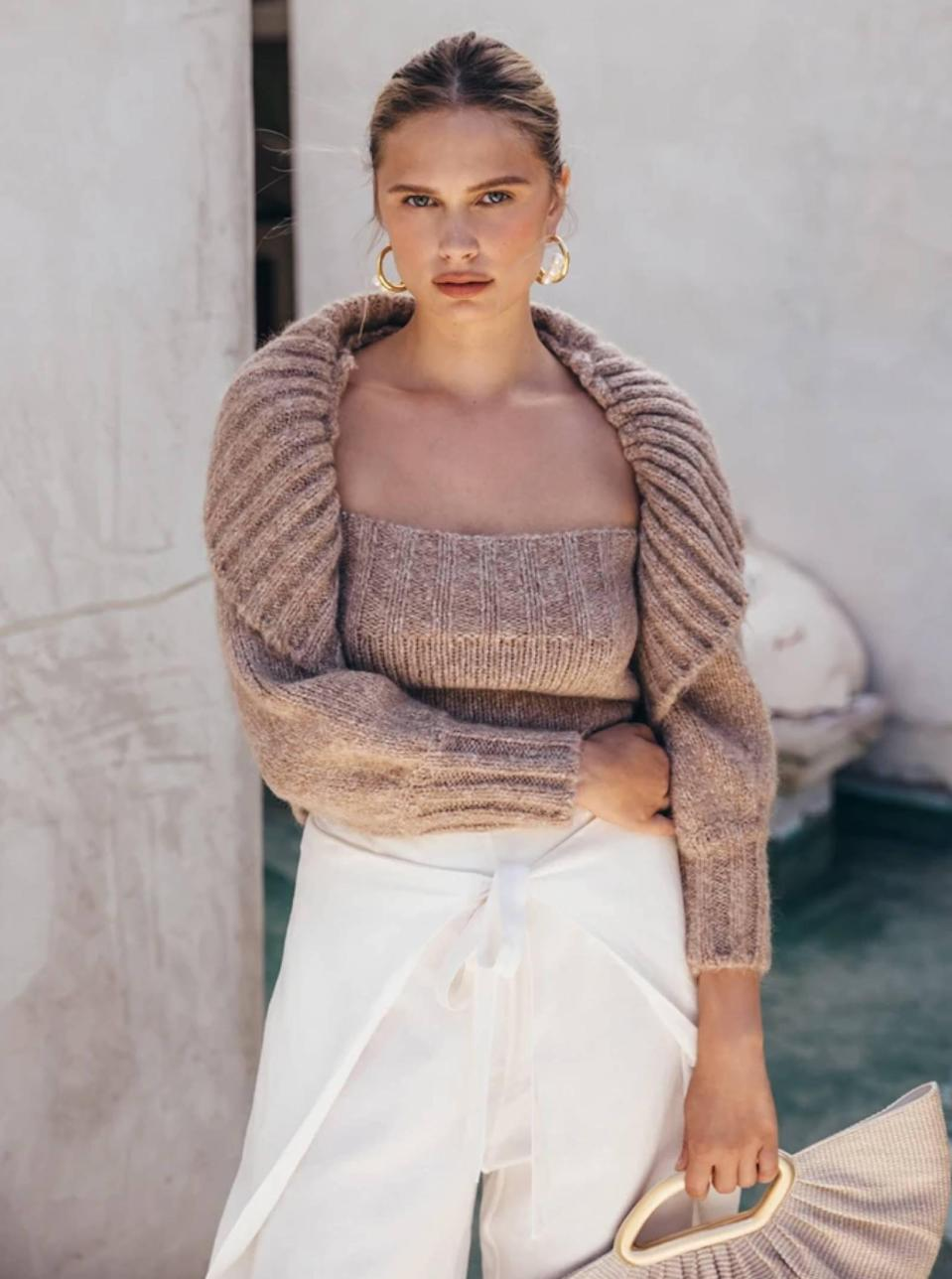 """Reach for this oatmeal shrug if your spring palette consists of creams and nudes. The oversized ribbed collar is everything—and since the knit is on the heavier side, you can totally wear this piece in the fall with <a href=""""https://www.glamour.com/story/cozy-cashmere-sets-to-buy-through-glamour-rewards?mbid=synd_yahoo_rss"""" rel=""""nofollow noopener"""" target=""""_blank"""" data-ylk=""""slk:cashmere joggers"""" class=""""link rapid-noclick-resp"""">cashmere joggers</a> or wide-leg jeans. $298, Cult Gaia. <a href=""""https://cultgaia.com/products/virginie-knit-top-light-camel"""" rel=""""nofollow noopener"""" target=""""_blank"""" data-ylk=""""slk:Get it now!"""" class=""""link rapid-noclick-resp"""">Get it now!</a>"""