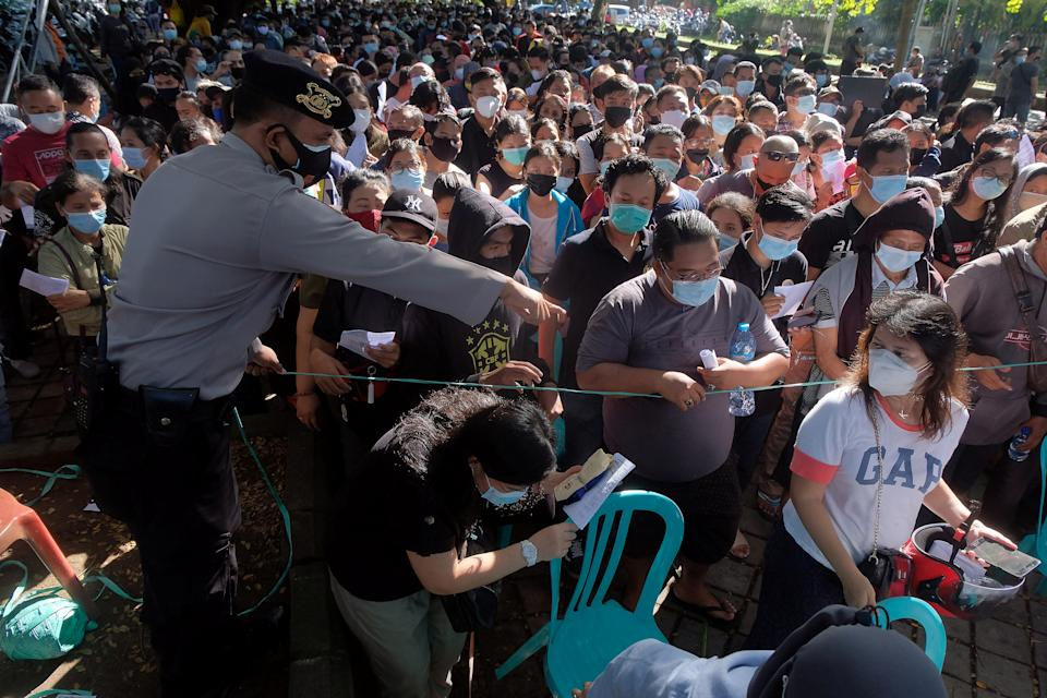 A police officer controls people as they queue for coronavirus disease (COVID-19) vaccine during a mass vaccination in Denpasar, Bali, Indonesia, June 26, 2021, in this photo taken by Antara Foto. Antara Foto/Nyoman Hendra Wibowo/ via REUTERS  ATTENTION EDITORS - THIS IMAGE WAS PROVIDED BY A THIRD PARTY. MANDATORY CREDIT. INDONESIA OUT.
