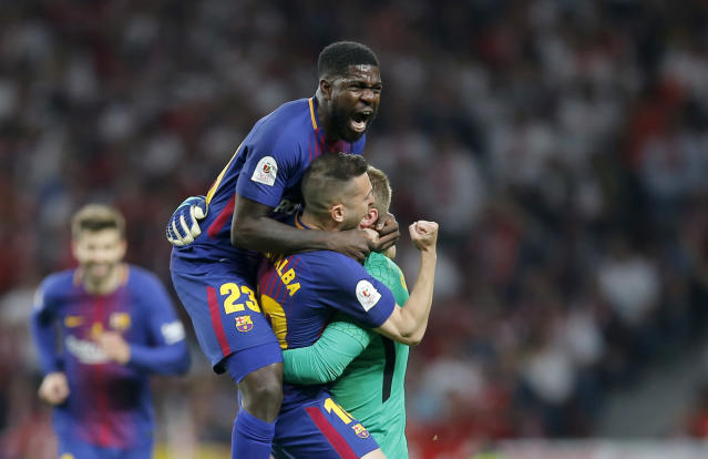Barcelona's Samuel Umtiti, top, Jordi Alba and goalkeeper Jasper Cillessen celebrate after Luis Suarez scoring his side's opening goal during the Copa del Rey final soccer match between Barcelona and Sevilla at the Wanda Metropolitano stadium in Madrid, Spain, Saturday, April 21, 2018. (AP Photo/Paul White)
